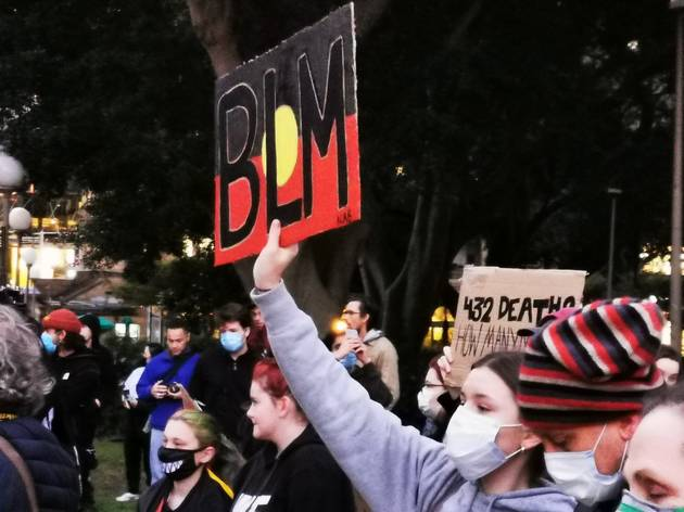 Woman holding sign that says BLM with an Aboriginal flag background