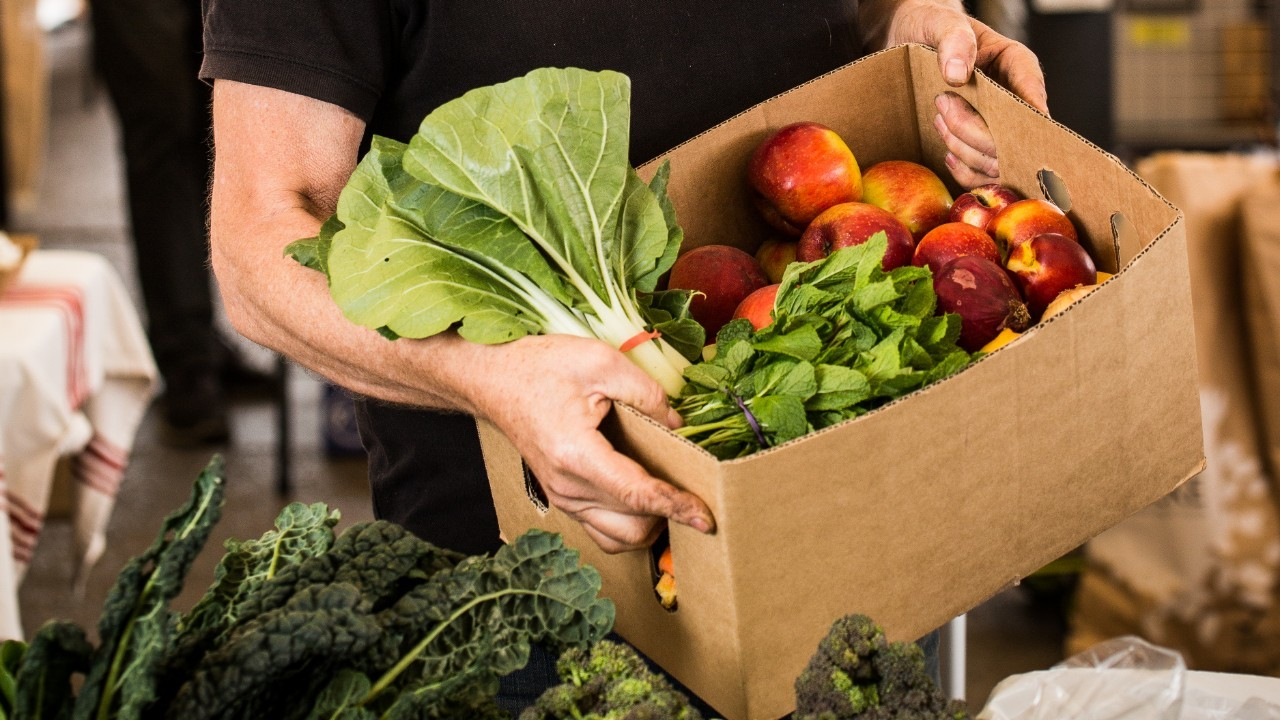 a stallholder holds up a cardboard box filled with fruit and vegetables