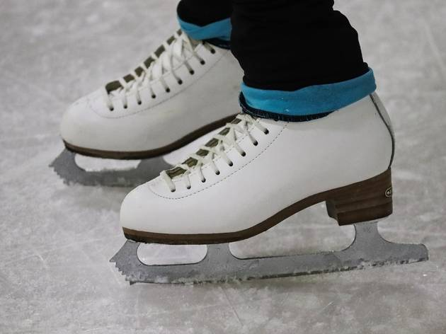 A pair of feet in ice skates on a rink