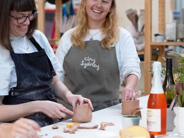 Two women laugh as they sculpt clay with wine and cheese on the table
