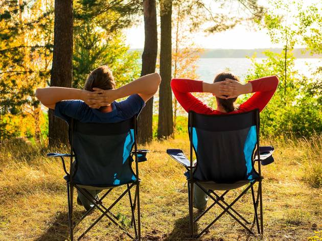 Couple in camping chairs by lake