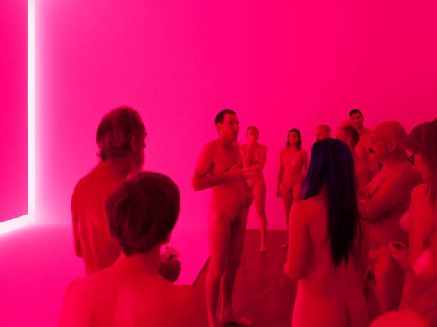 A group of naked adults standing around in a pink-lit room