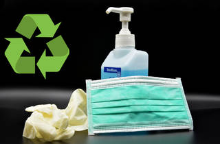 Hand sanitiser and a mask on a black background. A recycling symbol is next to them