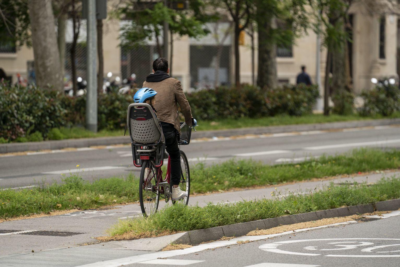 Un home circula pel carril bici amb el seu infant al seient de la bicicleta