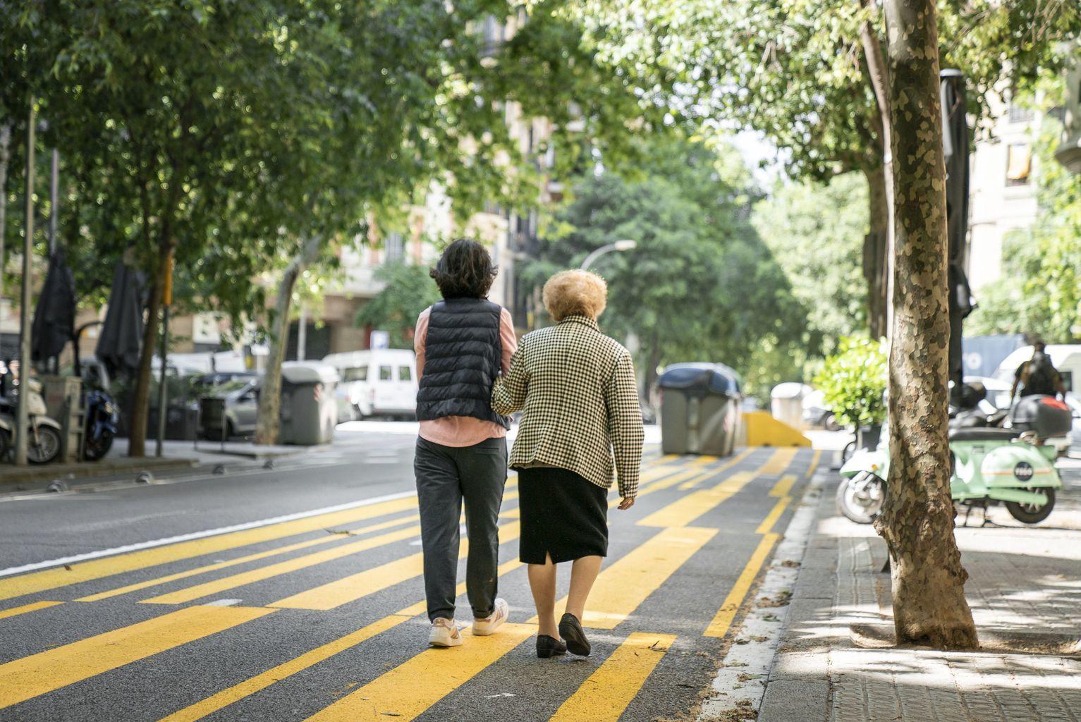 Una dona gran passeja de bracet d'una altra dona per un dels nous espais ampliats per a vianants i bicicletes
