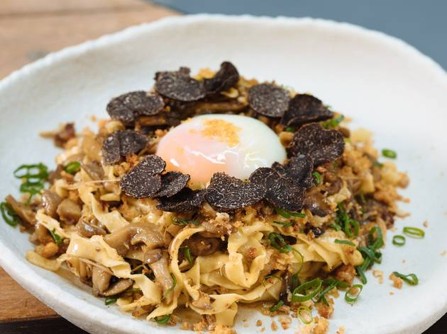 Bowl of noodles with egg and truffle on top