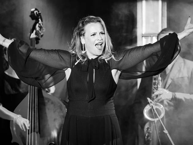 A black and white photo of Ali McGregor performing with a mic
