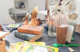 A table with items like books, a spoon, glass bottles and copper jugs on it