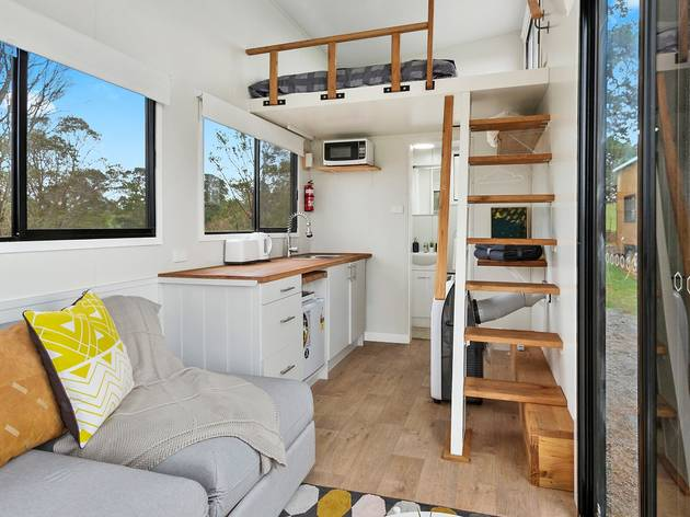 Interior of tiny home with kitchen and loft bed