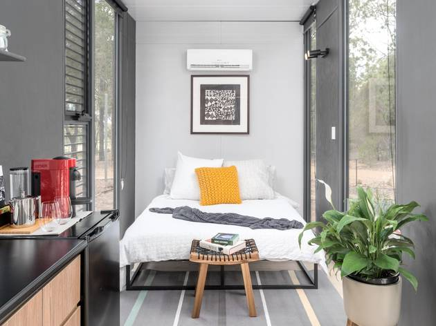 Interior of tiny home with bed and kitchen