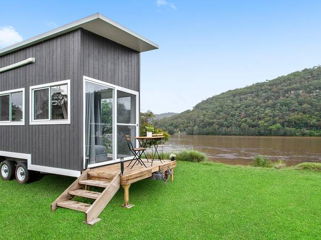 A tiny home mounted on a trailer sits by a river bank