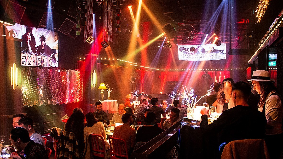 Image of venue with people sitting at tables, coloured lighting.