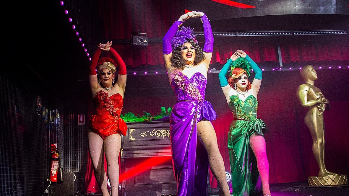 Three drag queens pose on stage in brightly coloured dresses