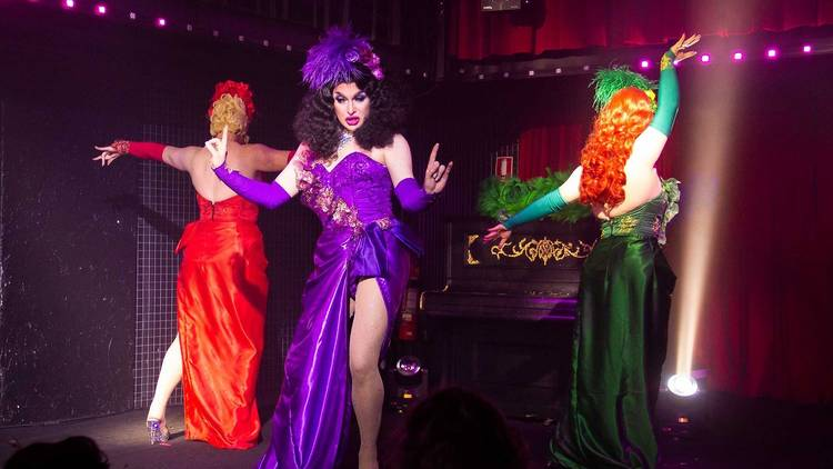 Three drag queens perform in brightly coloured dresses, one queen looks down at the audience with a saucy expression