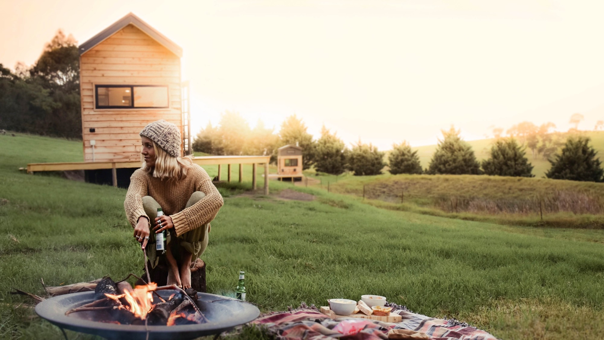 Woman roasts marshmallow on fire, there are two tiny houses behind her in a field.