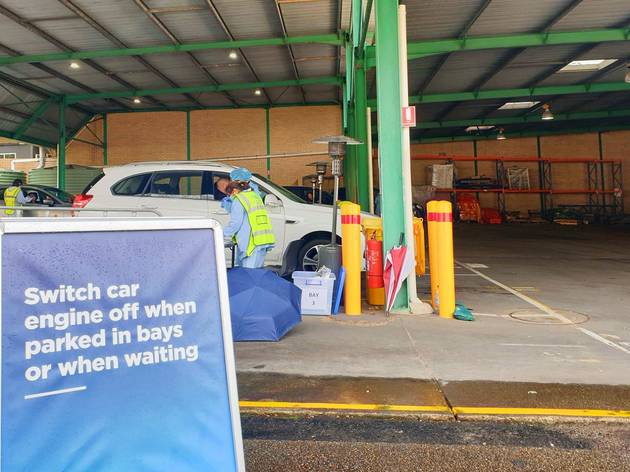 staff in medical gear speak to people in a parked car, a sign reads: 'Switch car engine off when parked in bays or when waiting'.