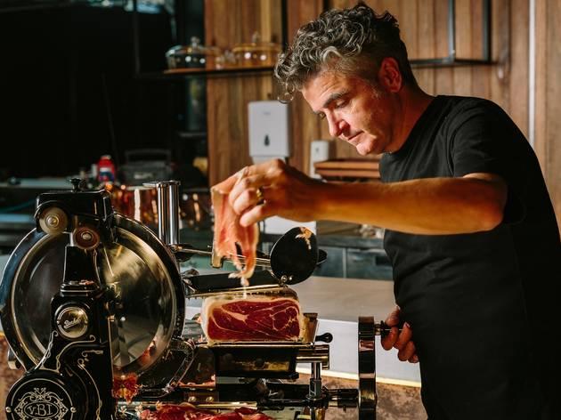 Chef feeding meat into a machine
