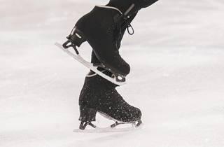 Feet in ice skates on rink