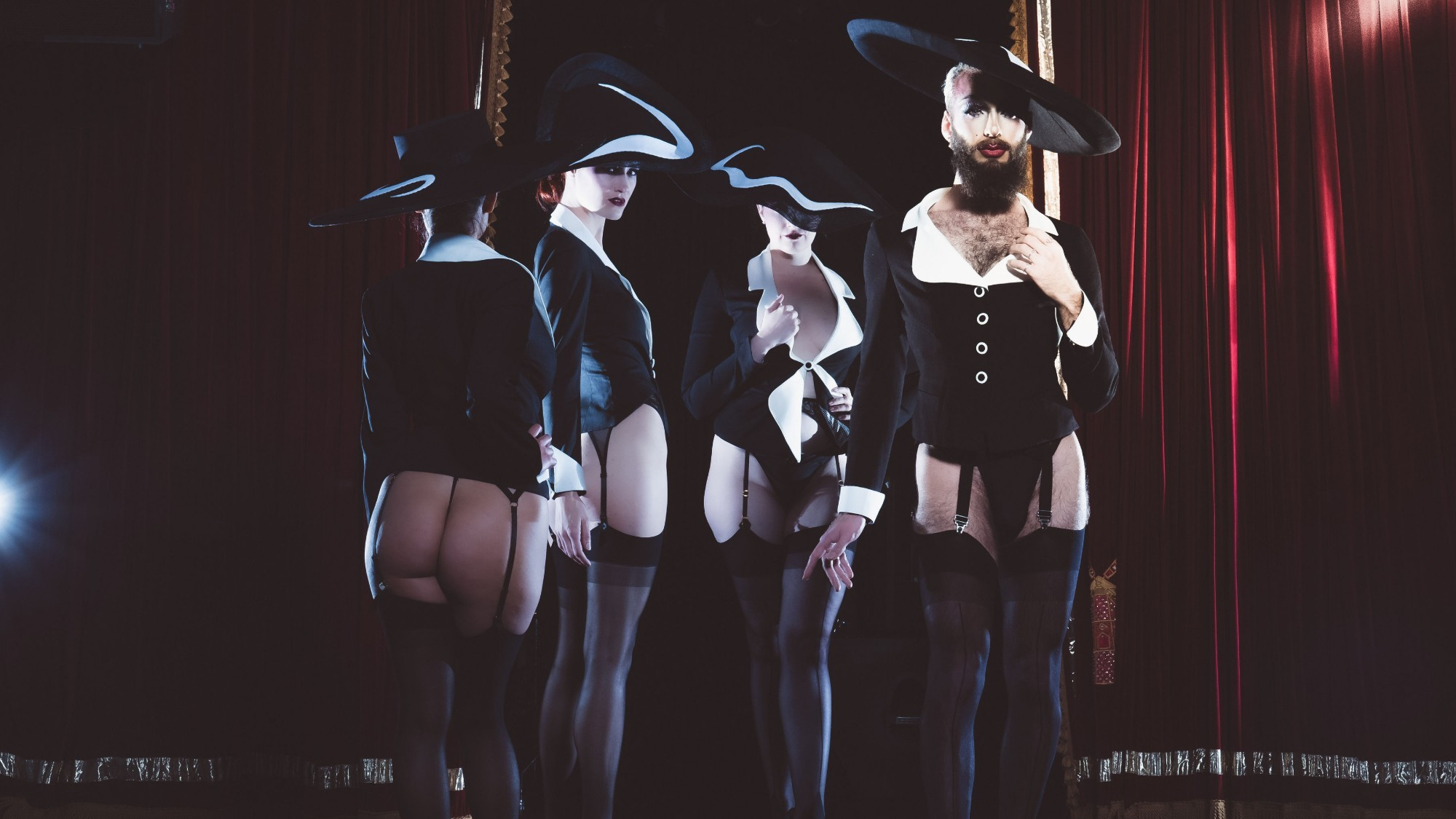 Four burlesque performers pose in black and white costumes with broad brimmed hats.