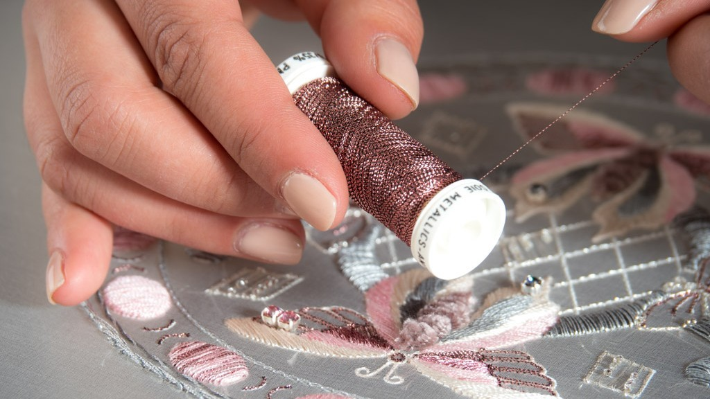 A manicured hand holds a spool of pink metallic embroidery thread over a half-complete broidery design with butterflies.