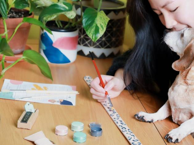 A woman and dog sit at a table, she is painting a collar, there are craft supplies on the table.