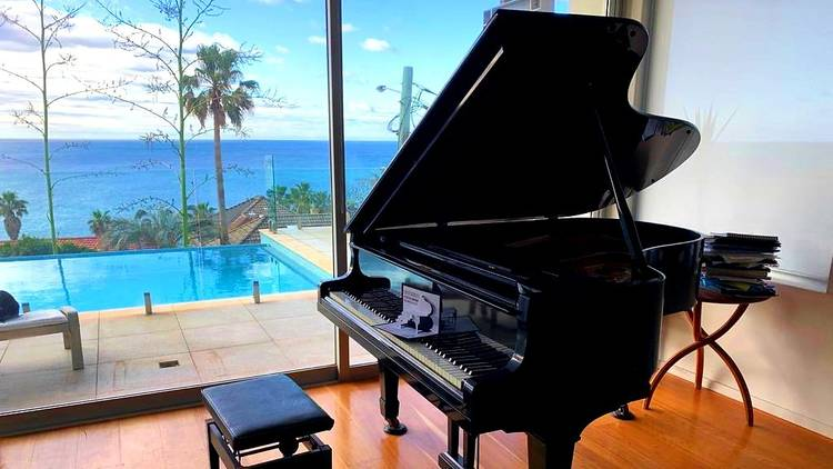 A black grand piano sits in a home, behind it a window reveals a pool and ocean views.