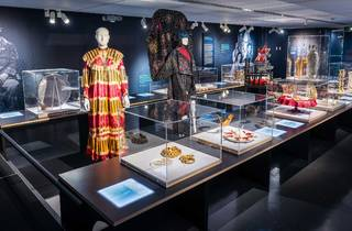 Interior of exhibit, ornate dresses at the centre surrounded by ritual objects.