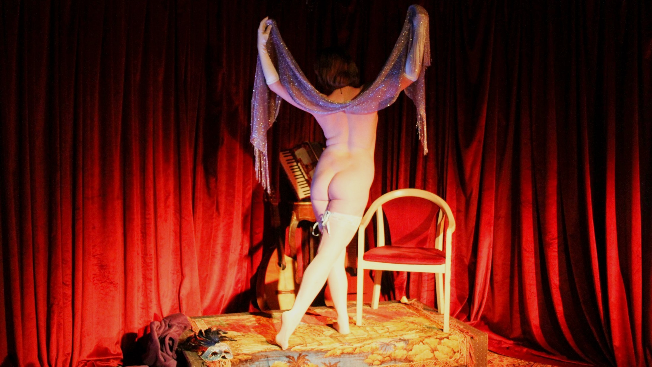 Nude model poses, she faces away from the camera holding a sparkly shawl in the air.