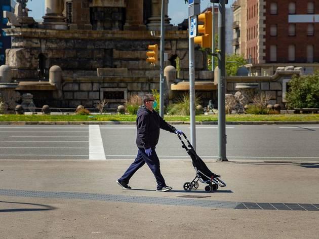 Home caminant sol amb mascareta per Barcelona
