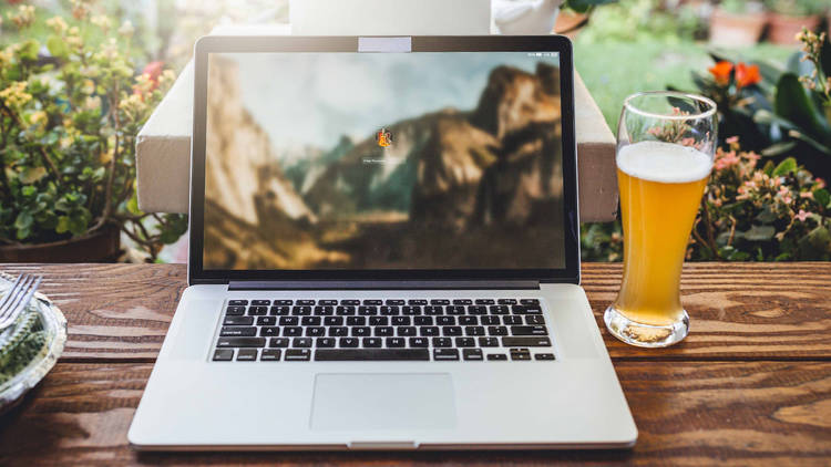 A laptop and glass of beer