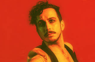 Artist Brendan Maclean wears tuxedo jacket, eyeliner, with red backdrop