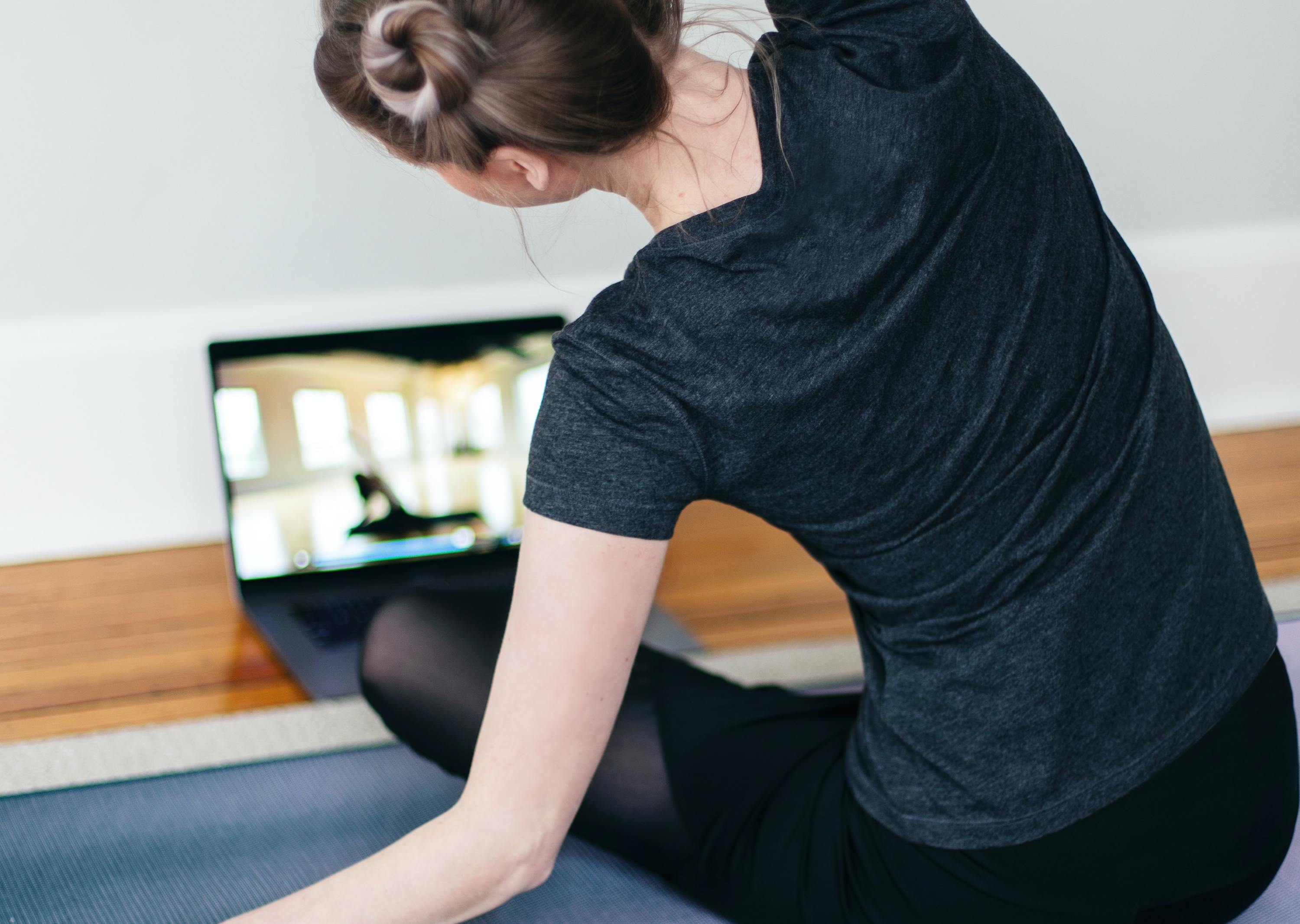 Woman stretches in front of laptop