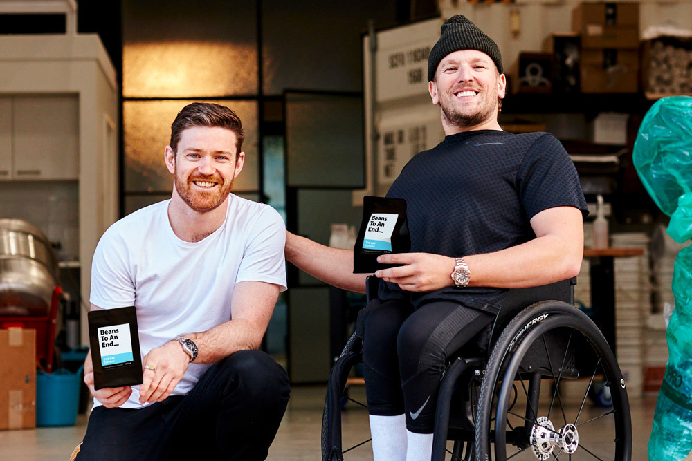 Beans to an End founder Matthew Jens with sportstar Dylan Alcott. Both are smiling and holding bags of coffee.