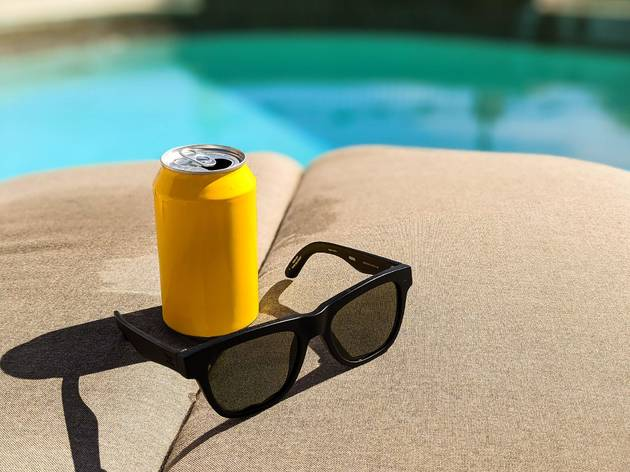 sunglasses and a beer on a pool lounger.