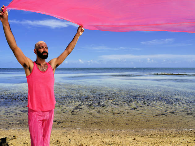 Daniel Gwirtzman on beach with pink fabric above his head