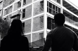 Dos personas ante construcción del Teatro Milán