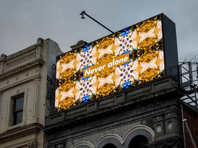 A digital billboard with a geometric pattern and the words 'Never alone'