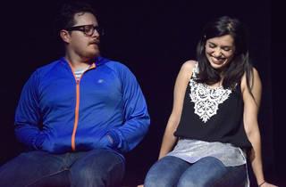 Actor y actriz sentados en el escenario de un teatro
