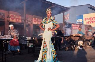 Photograph of person standing in a gown at a market