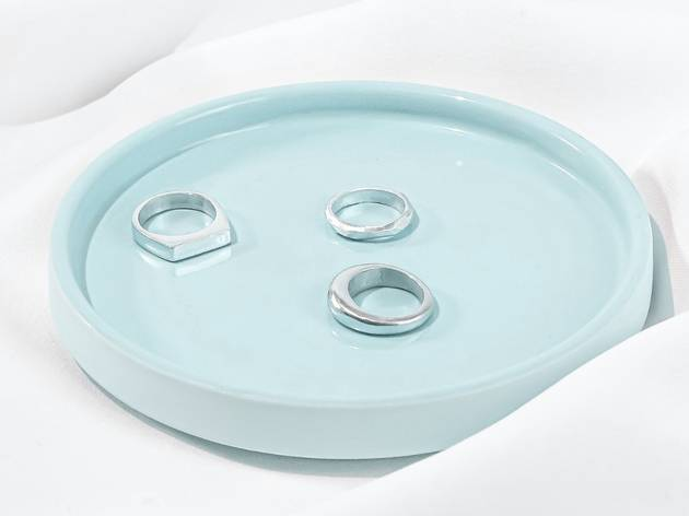 Three silver rings sit on a pastel blue tray