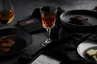 A dark table featuring plates of chocolate and dainty glasses filled with alcohol