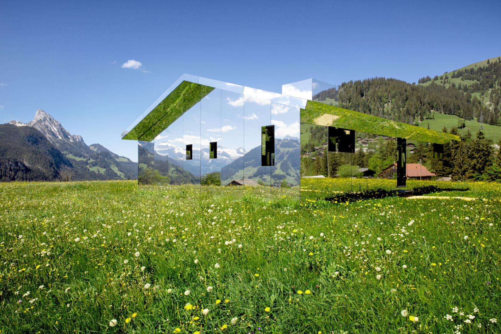 A mirrored house in the countryside, reflecting the scenery.