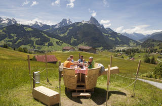 A family eating fondue at a table in the Swiss countryside.