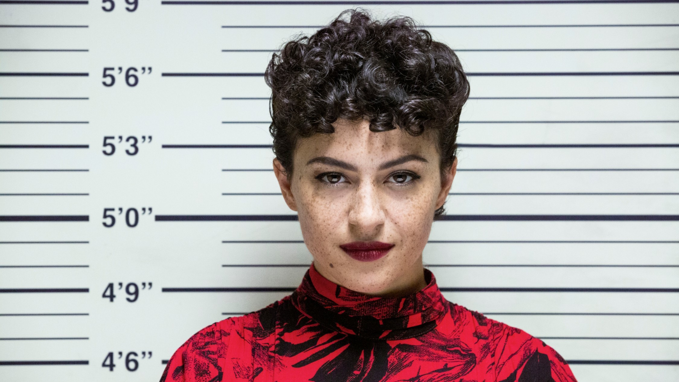 Alia Shawcat in front of a police booking height chart