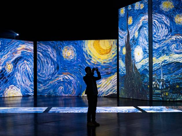 A silhouetted person in front of a huge projection of Vincent Van Gogh's The Starry Night