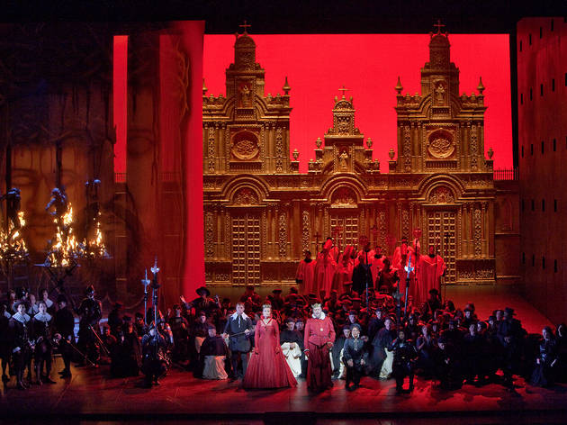 "A scene from Act 2 of Verdi's ""Don Carlo"" with Simon Keenlyside as Rodrigo, Marina Poplavskaya (in red) as Elisabeth, Ferruccio Furlanetto (in red) as Philip II, and Roberto Alagna (kneeling) in the title role. Taken during the rehearsal on November 16, 2"