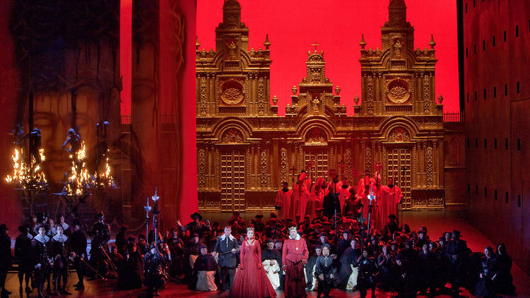 """A scene from Act 2 of Verdi's """"Don Carlo"""" with Simon Keenlyside as Rodrigo, Marina Poplavskaya (in red) as Elisabeth, Ferruccio Furlanetto (in red) as Philip II, and Roberto Alagna (kneeling) in the title role. Taken during the rehearsal on November 16, 2"""