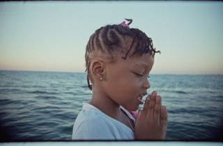 A child with the ocean behind her