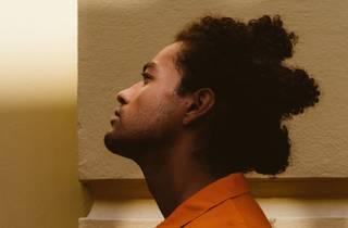 Indigenous rapper Ziggy Ramo in profile, wearing an orange top
