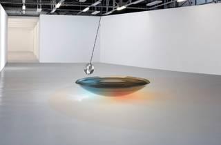 A pendulum swinging over an under-lit glass bowl
